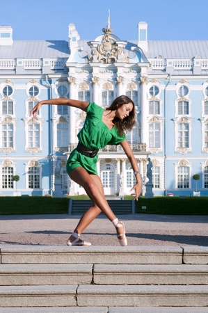 Beautiful ballerina is dancing outside with palace background photo