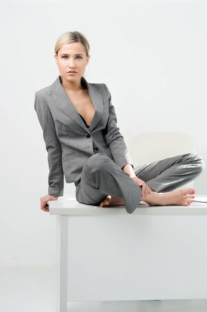 Young beautiful businesswoman is sitting on the table in the office. Break relaxing time photo