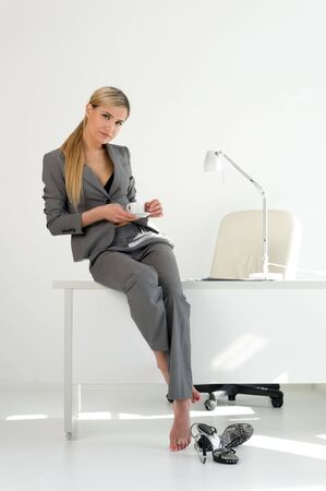 Young beautiful businesswoman is sitting on the table in the office. Break relaxing time Stock Photo - 9806025