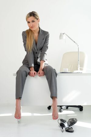 barefoot women: Young beautiful businesswoman is sitting on the table in the office. Break relaxing time