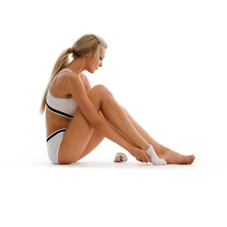 sport wear: Hermosa rubia en ropa de deporte lleva calcetines. Imagen aislado Foto de archivo
