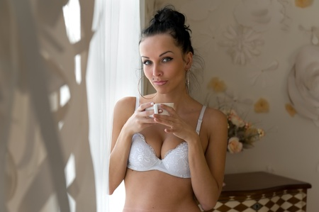 woman panties: Portrait of the beautiful woman. She is drinking tea at the window