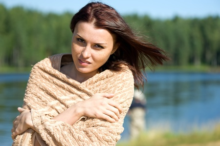 Portrait of the beautiful woman at the lake. She is wraping up in a towel. Summer time.  photo