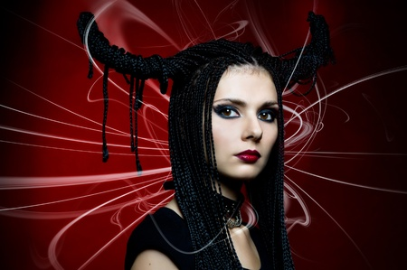 Art portrait. Woman in fansy devil shape. Horns. Halloween and Christmas theme photo