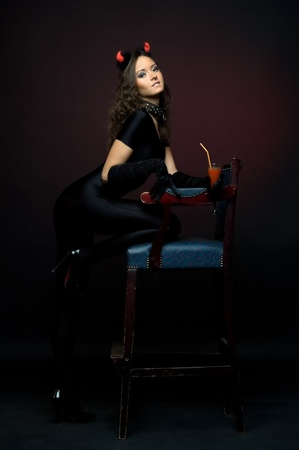 woman in fansy devil shape. With Horns and bloody coctail. Halloween and Christmas theme photo