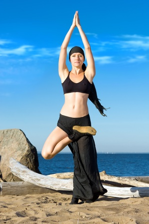 Young beautiful woman is making yoga exercises on the beach photo