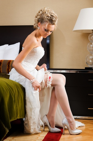 beautiful bride is sitting on the bed and trying the garter. photo