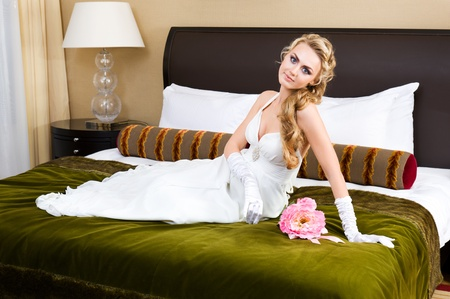 Beautiful woman in a wedding dress. She is in the bedroom with luxurious interior  photo
