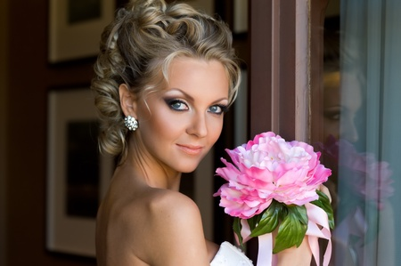 Beautiful bride is standing at the window with bunch of flowers. Stock Photo