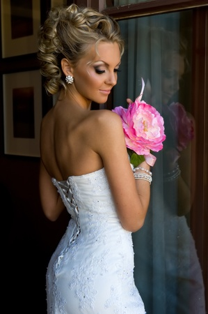 Beautiful bride is standing at the window with bunch of flowers. Stock Photo - 11268826