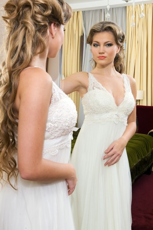 The bride in a wedding dress standing at the mirror photo