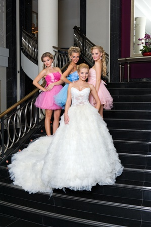 Beautiful bride with her  bridesmaids in the beautiful interior photo