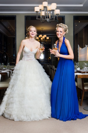 Beautiful Bride and her Bridesmaid with glasses of wine in a restaurant photo