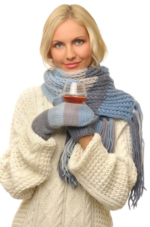 Portrait of the beautiful blonde woman with glass of cognac. She is dressed in warm clothes. Isolated image. photo