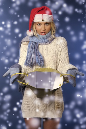 Beautiful blonde girl in winter clothes and santa hat with gift bag photo