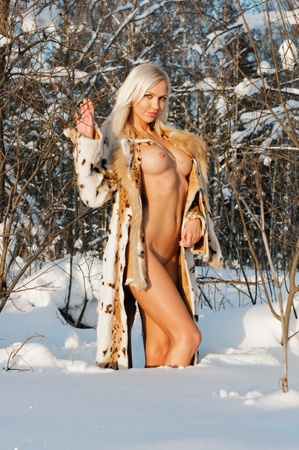 portrait of the beautiful naked blonde woman in winter forest.