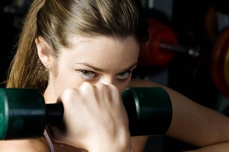 Torso of the beautiful woman is doing exercises with dumbbells in the sport club. photo