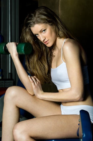 beautiful woman is doing exercises with dumbbells  in the sport club. photo