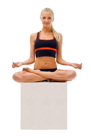 Beautiful woman is doing yoga exercises in the studio. Isolated image