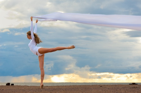 Beautiful ballerina dancing at the sea beach. photo