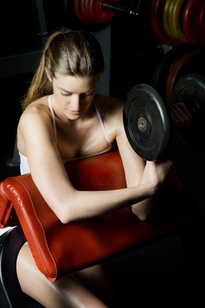 training device: beautiful woman is doing exercises with dumbbells  in the sport club. Stock Photo