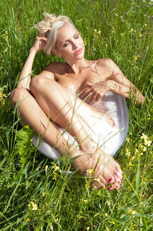 Summer meadow. Beautiful woman washing in the bath with camomile. photo