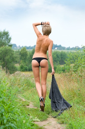 Beautiful naked woman walking at the meadow photo