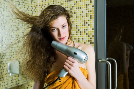 Beautiful woman drying her wet hair in the bathroom photo