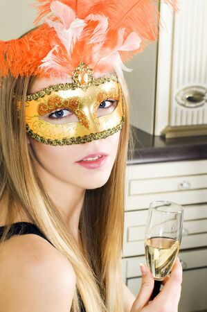 Woman in the interior. Beautiful blonde in a venetian mask. photo