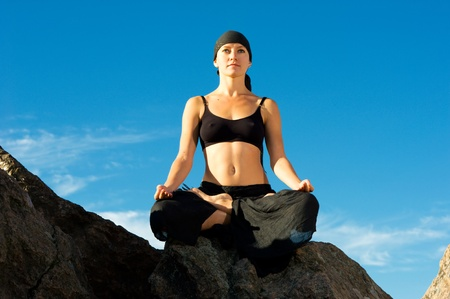 Young beautiful woman sitting in lotus pose on the beach photo