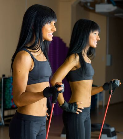Beautiful woman is doing exercises with the bar  the sport club. Stock Photo - 12440084