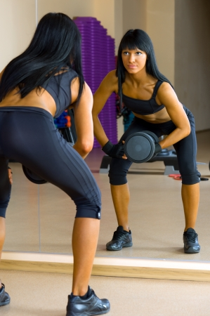 Beautiful woman is doing exercises with the bar  the sport club. Stock Photo - 12440092