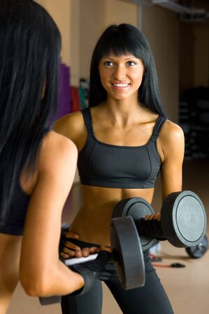 Beautiful woman is doing exercises with the bar  the sport club. Stock Photo - 12440087
