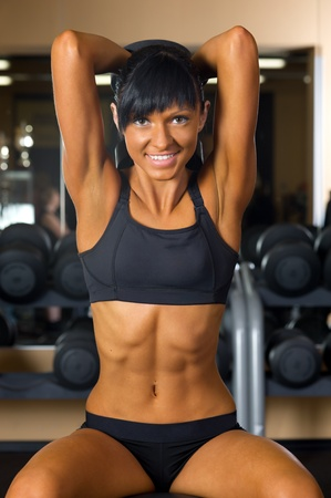 muscular build: Beautiful woman is doing exercises at the gym in the sport club.