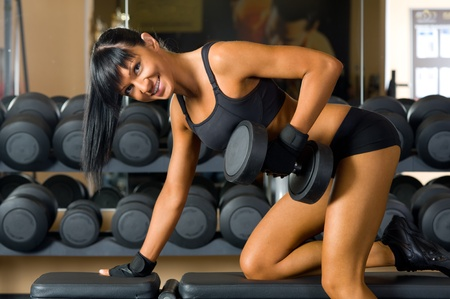 Beautiful woman is doing exercises with the bar  the sport club. photo