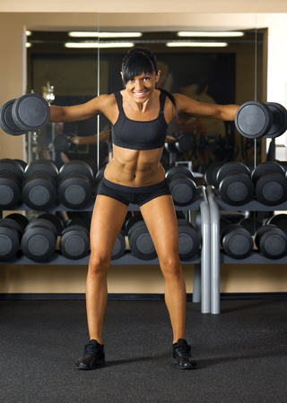 Beautiful woman is doing exercises with the bar  the sport club. Stock Photo - 12440086