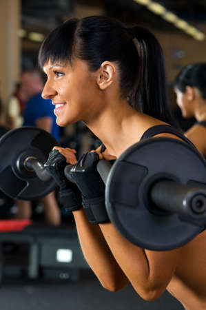 Beautiful woman is doing exercises with the bar  the sport club. Stock Photo - 12440089