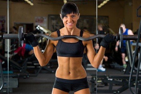 Beautiful woman is doing exercises with the bar  the sport club. Stock Photo - 12440088