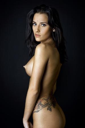mujer desnuda de espalda: Detrás de la hermosa mujer desnuda con el tatuaje. Foto con el fondo oscuro.