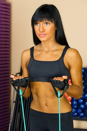 training device: Beautiful woman is doing exercises at the gym in the sport club.