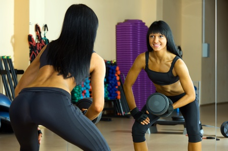 Beautiful woman is doing exercises with the bar  the sport club. Stock Photo - 12440177