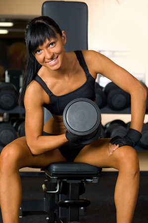 Beautiful woman is doing exercises with the bar  the sport club. Stock Photo - 12440214