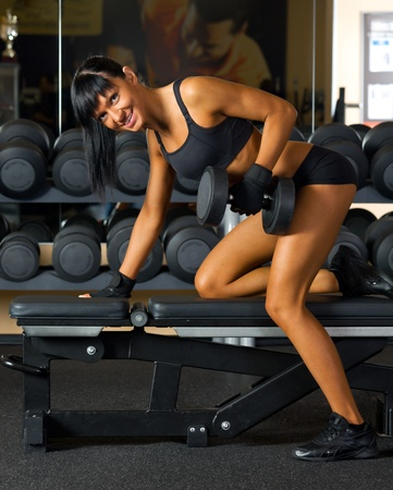 Beautiful woman is doing exercises with the bar  the sport club. Stock Photo - 12440215