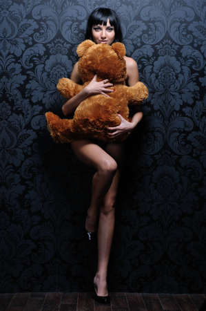 nude woman back: Beautiful naked girl is holding the teddy bear
