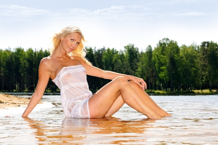nude wet: Beautiful young woman on the beach sitting at the waterline. Stock Photo