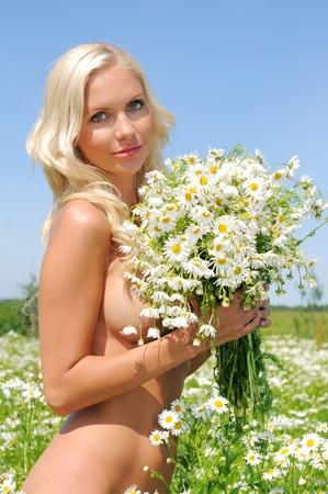 mujer desnuda: hermosa mujer desnuda en la pradera con el manojo de manzanilla.