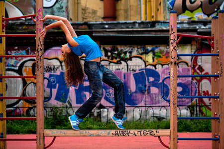 urban dance: Portrait of the beautiful young woman with wall graffiti background . Street photoshoot .