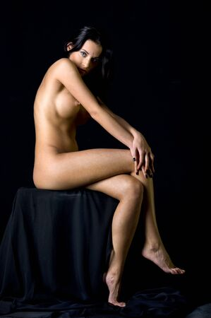 Beautiful naked woman sitting in the dark studio.