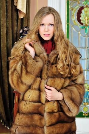 bontjas: Portret van de mooie vrouw in bontjas. De luxe klassieke inrichting. Stockfoto