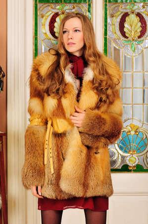 Portret van de mooie vrouw in bontjas. De luxe klassieke inrichting. Stockfoto